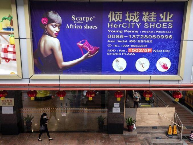 Une femme passe devant un panneau d'affichage dans une partie de la ville où la plupart des Africains vivent et travaillent à Guangzhou, dans la province du Guangdong, en Chine, le 13 avril 2020.