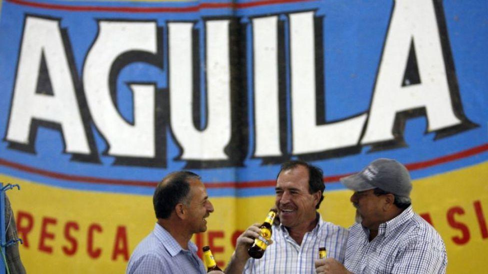 Tres hombres conversan mientras toman una cerveza Águila.