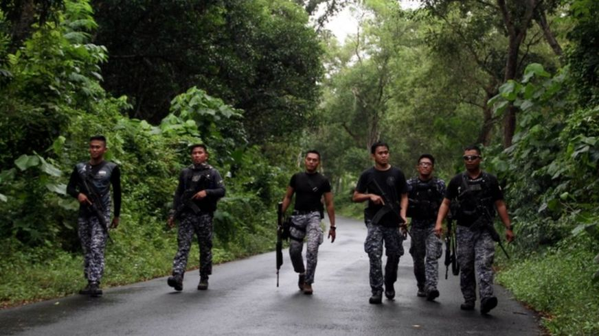 Prison personnel patrol during a manhunt for more than 150 inmates who escaped after gunmen stormed a prison in North Cotabato province, southern Philippines