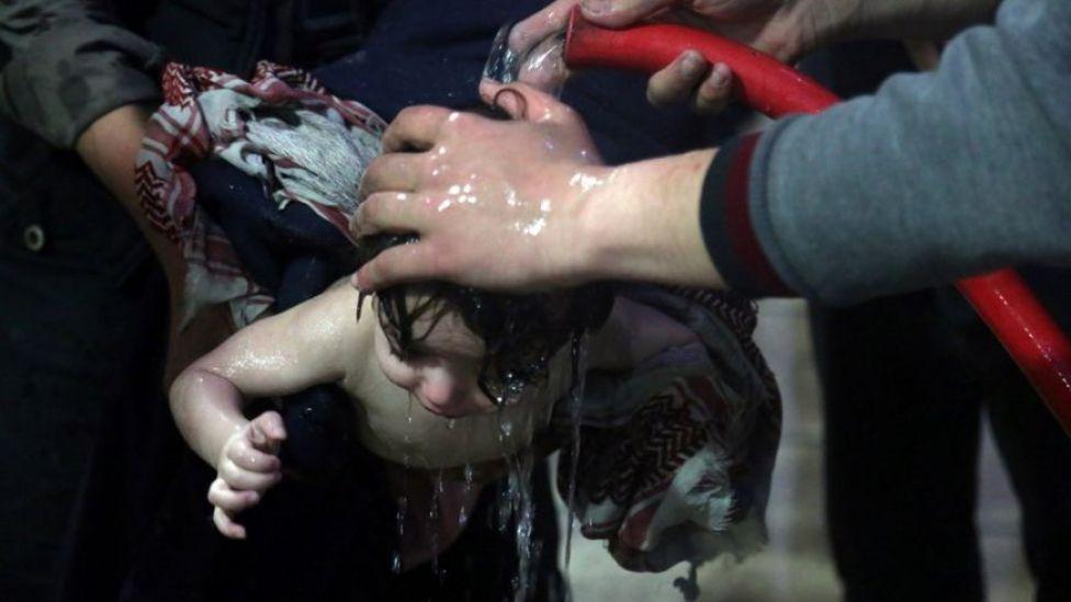 Un niño es bañado con abundante agua en un hospital tras el supuesto ataque químico en Douma.