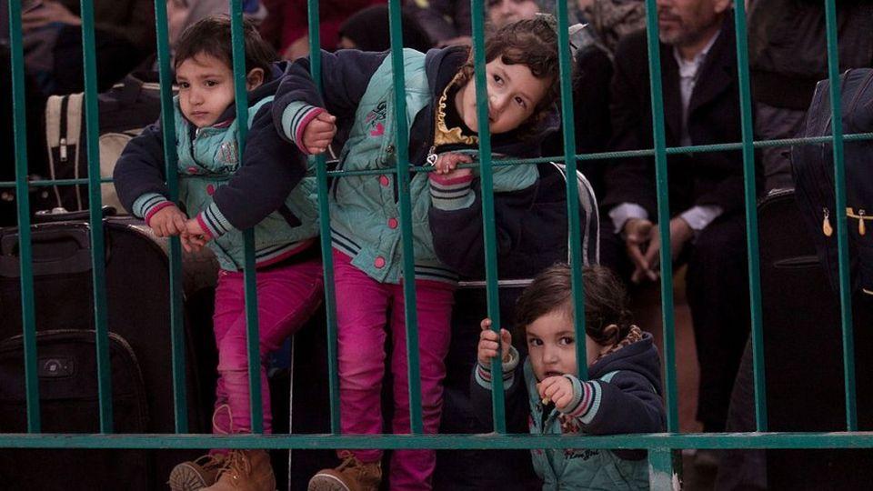 Niños esperan en el cruce fronterizo de Rafah, entre Gaza y Egipto