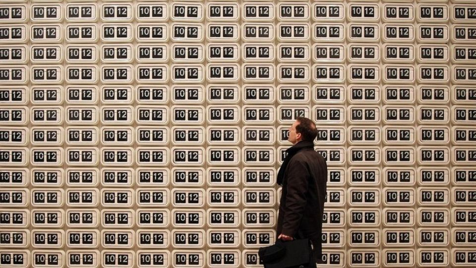 """Un hombre mirando una pared """"empapelada"""" de relojes que marcan la misma hora"""