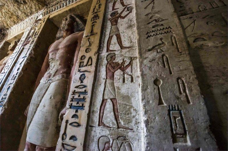 Coloured statues and hieroglyphs inside the tomb at Saqqara