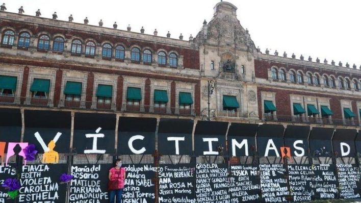 """A woman stands next to placards with names of women victims of violence as preparations to the Women""""s International Day in Mexico City, Mexico, 07 March 2021"""