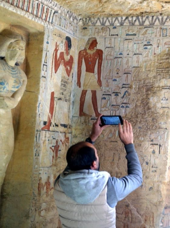 A man takes photos of the well-preserved hieroglyphs inside the newly-discovered tomb of Wahtye