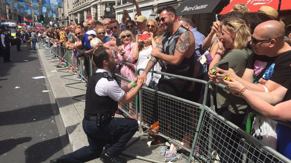 Police officer proposing to his boyfriend at Pride