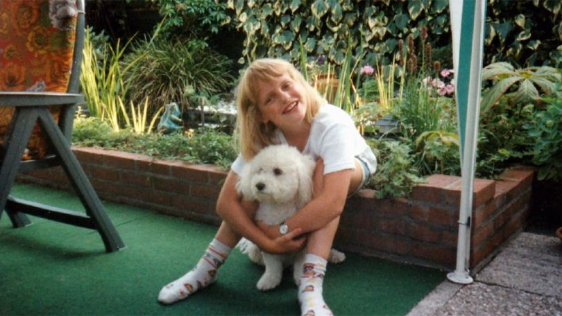 Aurelia Brouwers na infância. Na imagem, ela aparece abraçada a um cachorro, sorrindo para a câmera