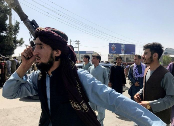 A member of Taliban forces inspects the area outside Hamid Karzai International Airport in Kabul
