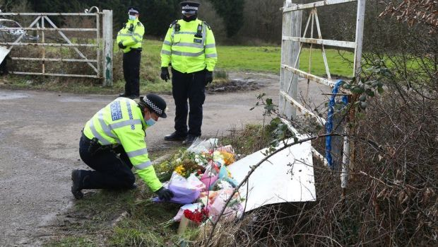 A police officer lays flowers left by members of the public
