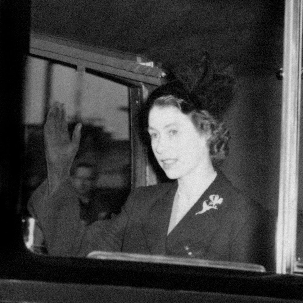 Queen Elizabeth II, in a black mourning outfit, waving as she returns to Clarence House in London the day after she became Queen
