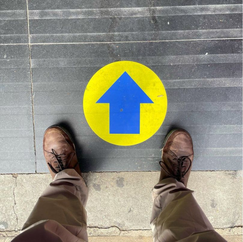 A yellow and blue sign with an arrow