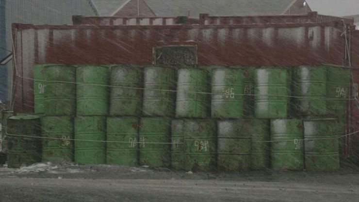 Fuerte nevada y barriles verdes al fondo