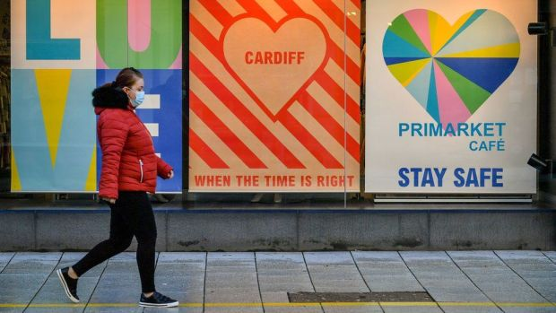 Woman walking past posters in Cardiff