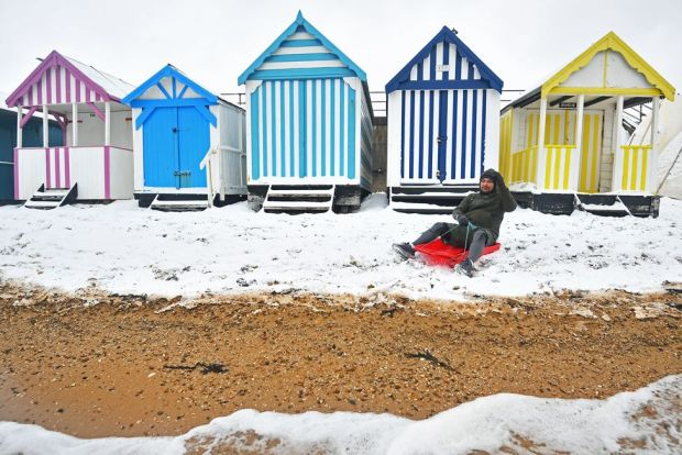 A man sits on a sledge on the snow-covered beach at Thorpe Bay, Essex, on 9 February 2021