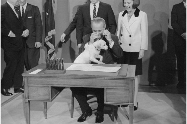 President Johnson tries to sign a bill on his desk whilst with his pet dog Yuki sits on his lap