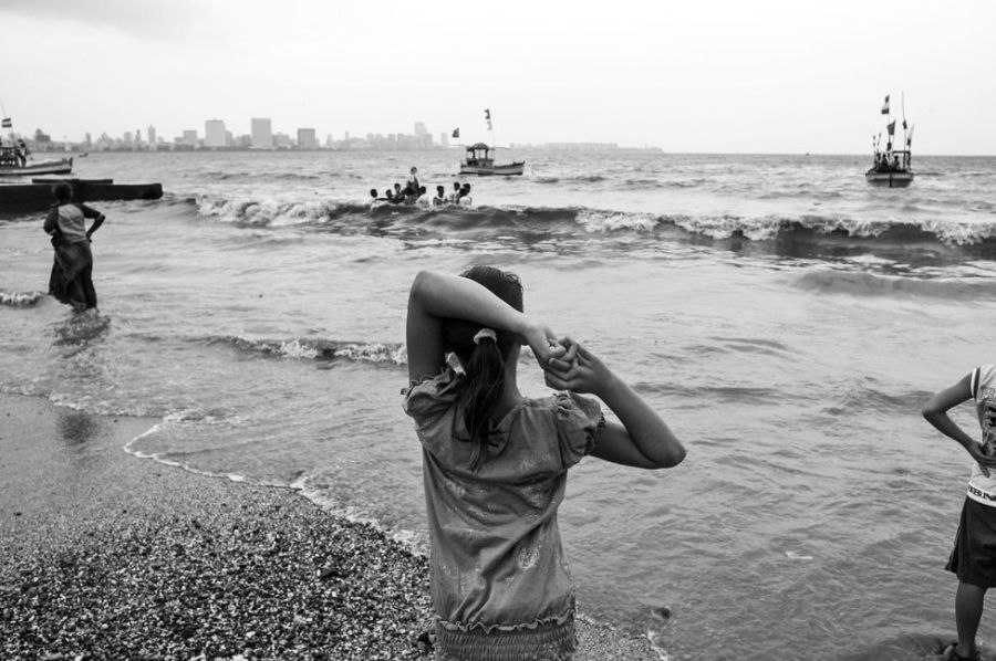 A girl looks at the ocean while standing on a beach in Mumbai