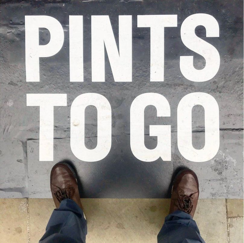 A sign on the ground declaring 'Pints To Go'