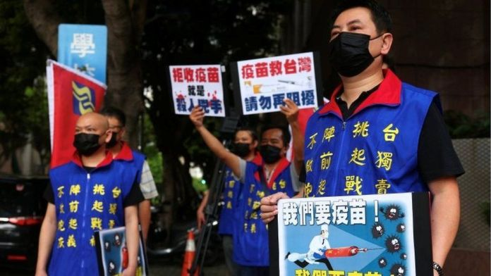 People hold placards calling for Taiwan government to allow the use of COVID-19 vaccines from China, in front of the Taiwan Centers for Disease Control building, following the recent spike in coronavirus disease infections in Taipei, Taiwan, May 24, 2021.