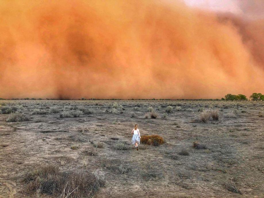 ニューサウスウェールズ州のMullengudgeryで砂嵐に向かって走っている子供