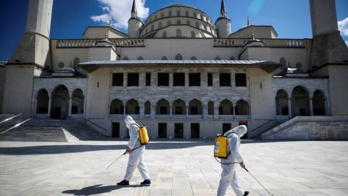 Municipality workers in protective suits disinfect courtyard of the Kocatepe Mosque