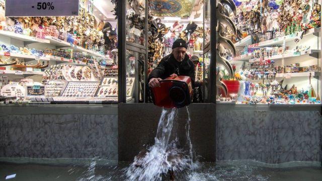 Sprzedawca używa wiadra do usuwania wody ze swojej nieruchomości w Wenecji, 13 listopada 2019 r