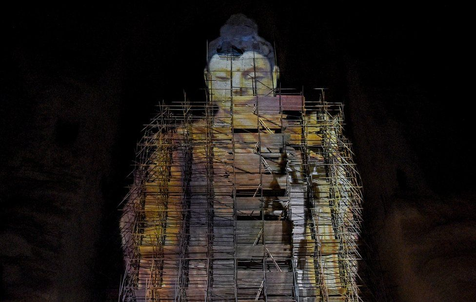A close-up shot of the Salsal Buddha, projected in the void where it used to stand