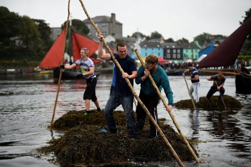 Two men push a seaweed raft using sticks.