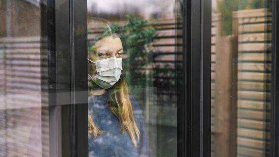 Woman stands behind window wearing face mask