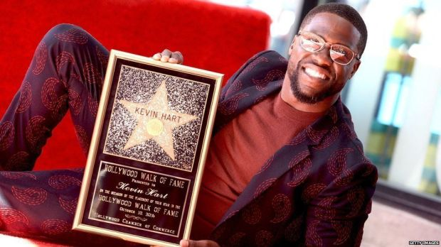 Kevin Hart holding his Hollywood Walk of Fame plaque