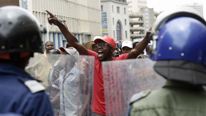 Police officers watch supporters of Zimbabwe's Movement For Democratic Change (MDC) gathering outside the party's headquarters in the capital, Harare