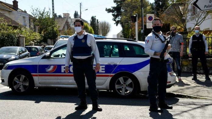 French police officials close a street near a police station in Rambouillet, south-west of Paris, on April 23