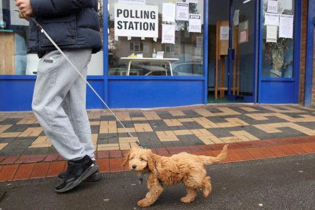 A man walks with a dog past a polling station in Oxford