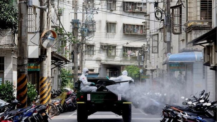 Soldiers wearing protective suits disinfect a street from a vehicle following the recent surge of coronavirus disease (COVID-19) infections, in Tucheng district of New Taipei City, Taiwan May 27, 2021.