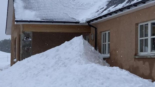 Snow stacks up against a house in Lumphanan in Aberdeenshire