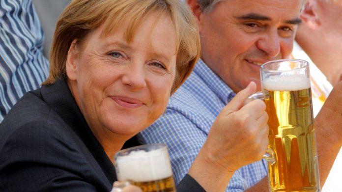 Kancelarja gjermane Angela Merkel (L) dhe Peter Mueller, kryeministër federal i rajonit Saar dhe kandidati kryesor i partisë konservatore të Unionit Kristian Demokratik (CDU) për zgjedhjet e ardhshme të shtetit Saarland, mbajnë gota birrë gjatë një tubimi të fushatës elektorale në Bosen pranë Saarbruecken 15 gusht 2009