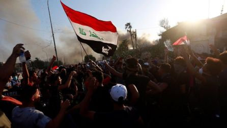 Protesters carrying an Iraqi flag gather near a government building in Basra