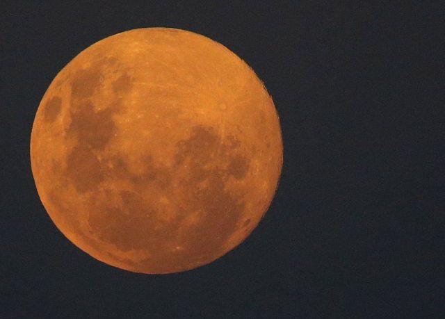 A full moon appears orange in the night sky.