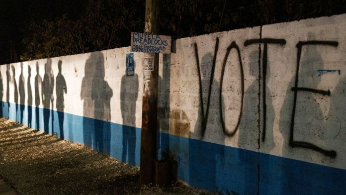 """The silhouettes of people queueing up to vote seen on a wall with the word """"Vote"""" painted on it - Thursday 12 August 2021"""