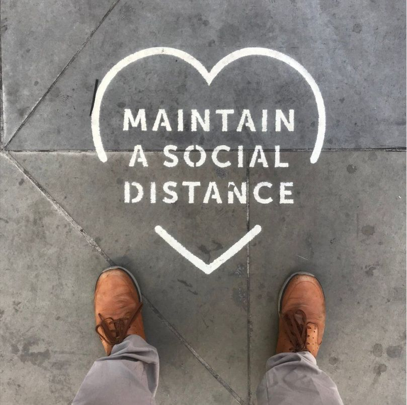 A stencil outline on the ground asking people to maintain social distancing