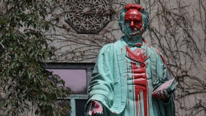 Red paint covers the defaced Ryerson University statue of Egerton Ryerson