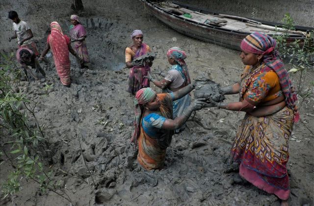 A group of women pass material to each other to build a dam in India