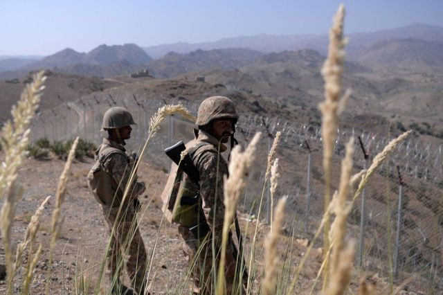 Pakistani soldiers keep vigil next to a newly fenced border fencing along Afghan border at Kitton Orchard Post in Pakistan's North Waziristan tribal agency on October 18, 2017.