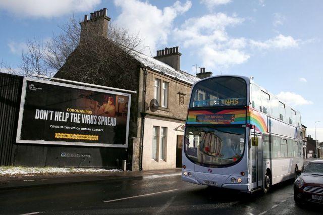 Bus passing coronavirus poster