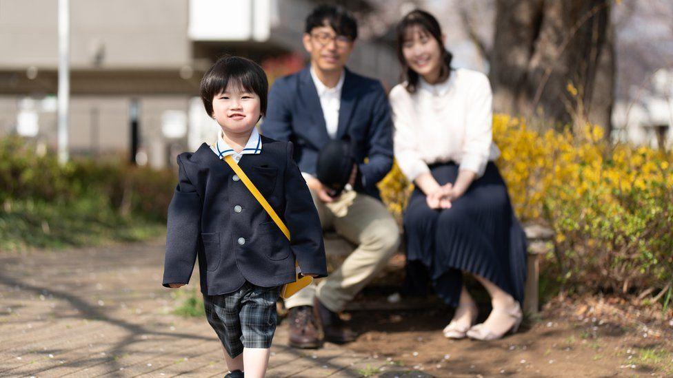 Uma menina japonesa vai para a escola enquanto seus pais a observam