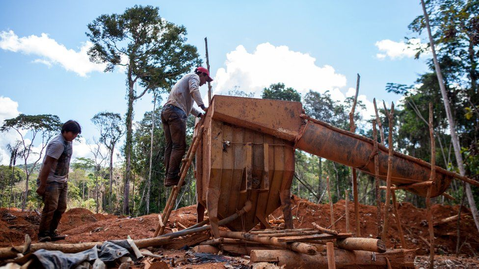 Two men are working a machine in a deforested area