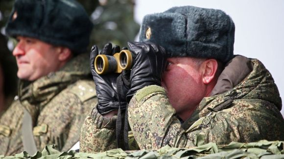 Russian solider looks through a pair of binoculars