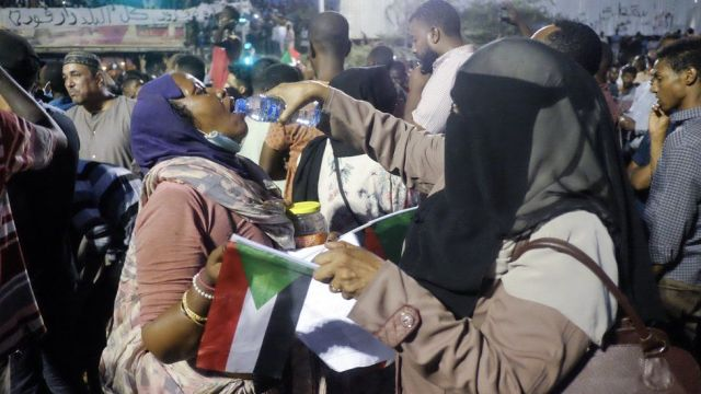 A woman wearing a headscarf and face veil pours water into the mouth of another protester at a sit-in at the military HQ in Khartoum, Sudan - Sunday 7 April 2019