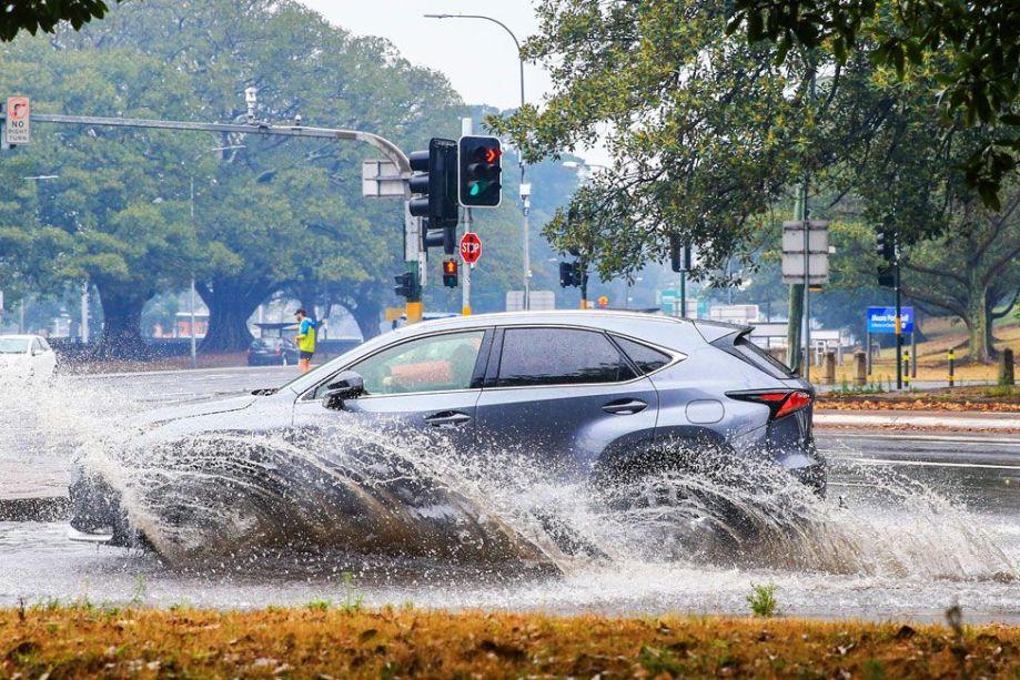 シドニーのサリーヒルズの浸水した通りを車が走っているのが見られます。 1月20日