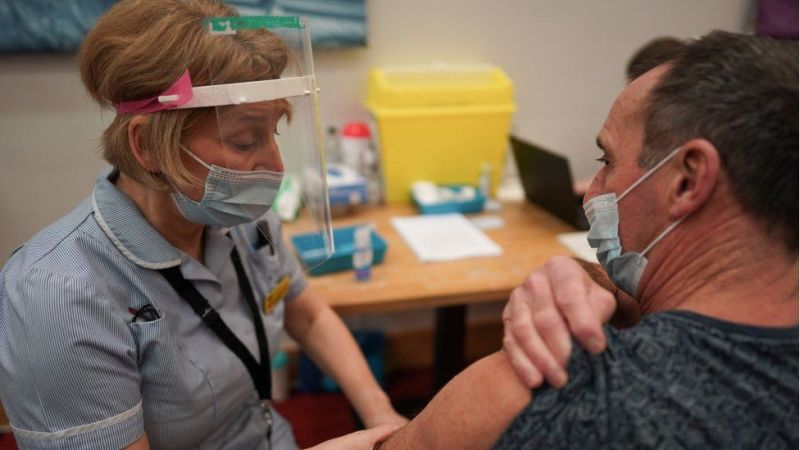 A key worker receives the vaccine in the UK
