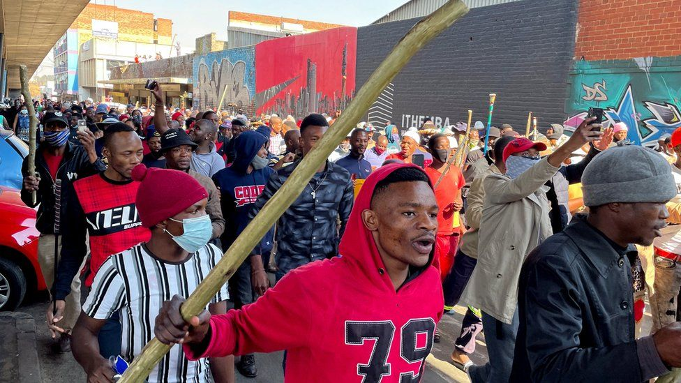 """Stick-wielding protesters march through the streets as violence following the jailing of former South African President Jacob Zuma spread to the country""""s main economic hub in Johannesburg, South Africa, July 11, 2021."""
